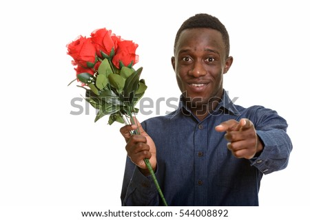 Young happy African man smiling and pointing finger while holding red roses ready for Valentine's day isolated against white background
