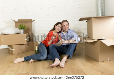young happy American couple sitting on floor unpacking boxes together celebrating with champagne toast moving in a new house or apartment in real estate and independent lifestyle concept