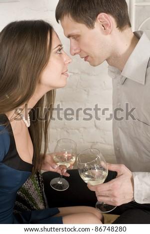Young happy amorous couple celebrating with white wine - stock photo