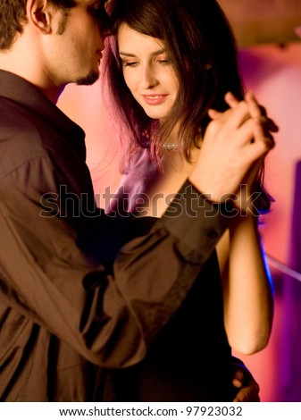 Young happy amorous couple dancing on romantic date at restaurant or club