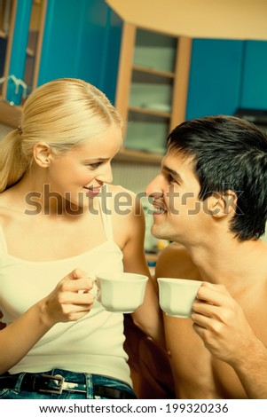 Young happy amorous couple drinking coffee together at home - stock photo
