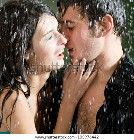 Young happy amorous couple hugging and kissing under a rain, outdoors