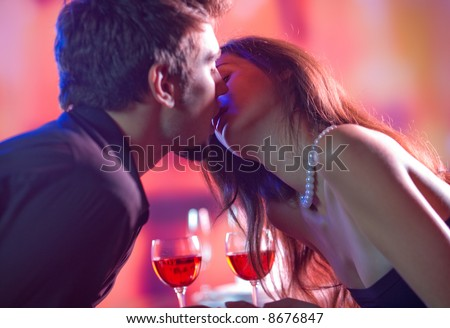 Young happy amorous couple kissing at restaurant - stock photo