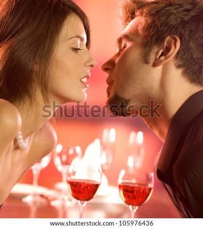 Young happy amorous couple kissing on romantic date, at restaurant - stock photo