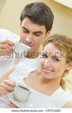 Young happy amorous couple with coffee drink at home - stock photo