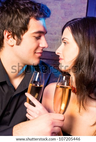Young happy amorous couple with glasses of champagne on romantic date at restaurant or club - stock photo