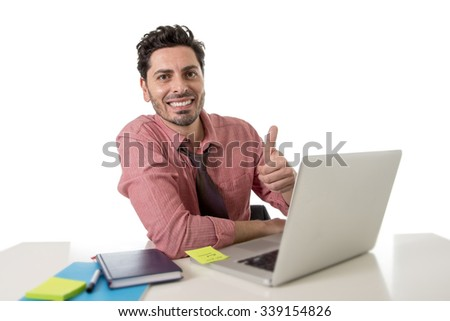 young happy and attractive businessman in shirt and tie sitting at office desk working with computer laptop giving thumb up feeling relaxed and satisfied smiling in business success concept  - stock photo