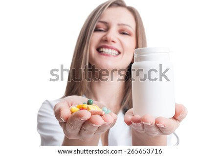 Young , happy and friendly female doctor offering pills and holding a white container or bottle - stock photo