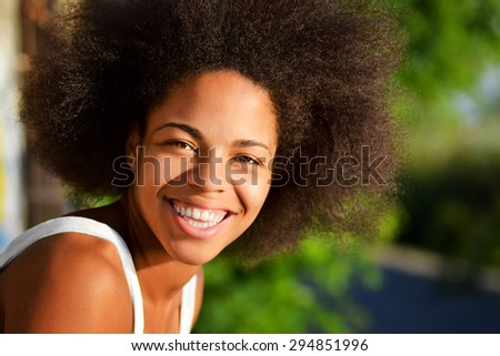 young happy and  pretty afro woman closeup portrait  on natural background - stock photo