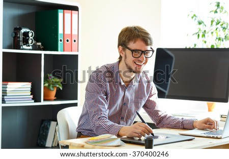 Young happy artist drawing something on graphic tablet at the home office