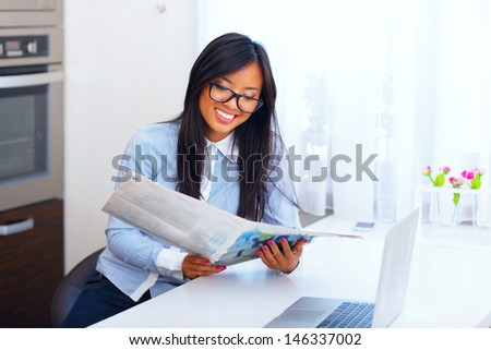 Young happy asian businesswoman reading newspaper at home