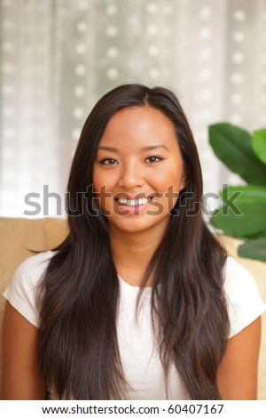 Young happy asian girl sitting in the living room smiling
