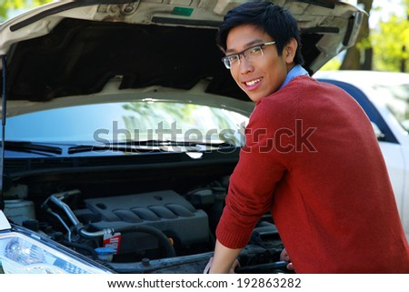Young happy asian man checking his car engine - stock photo
