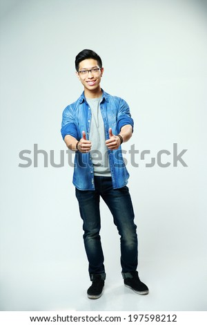 Young happy asian man showing thumbs up on gray background - stock photo