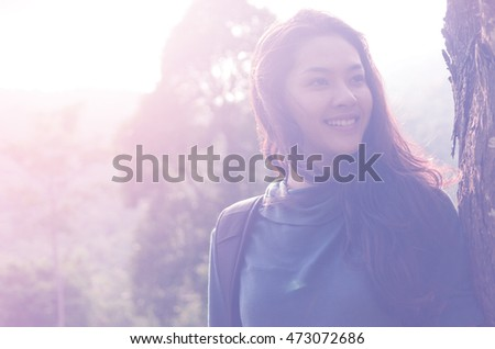 Young happy Asian woman travel though a nature forest, happy smiley face.