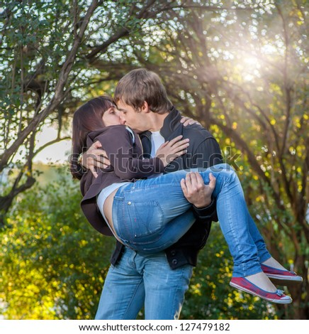 Young happy attractive couple kissing, outdoors - stock photo