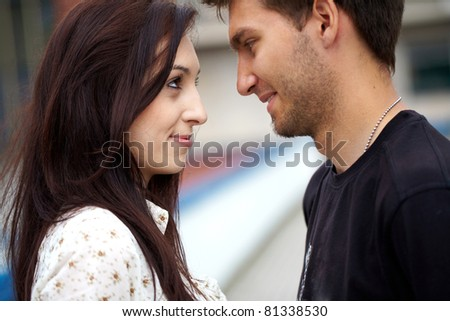 young happy attractive couple looks into each other eyes, outdoor shoot - stock photo