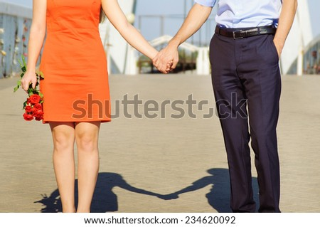 Young happy attractive couple walking together, outdoors - stock photo