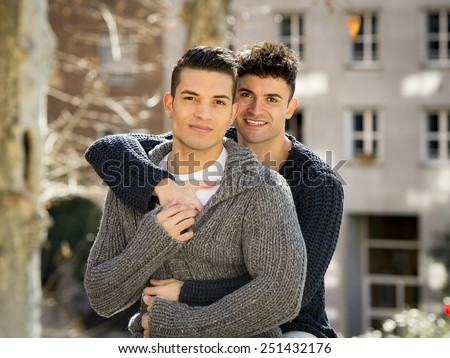 young happy attractive gay men couple cuddling posing outdoors on street in sexual freedom and free homosexual love concept in urban background - stock photo