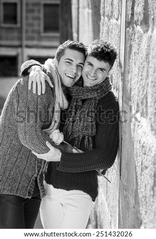 young happy attractive gay men couple holding  rose hugging outdoors on street in free homosexual love concept in Valentines day on urban background black and white - stock photo
