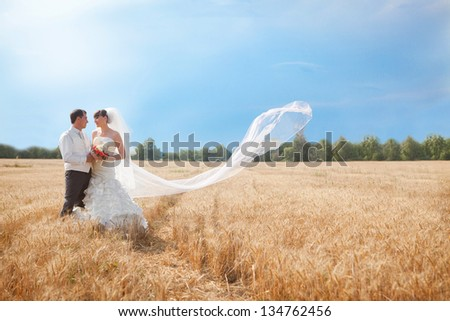 Young happy attractive married couple playful in wheat field after wedding - stock photo