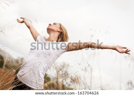 young happy attractive woman arms wide open nature outdoor breathing  - stock photo