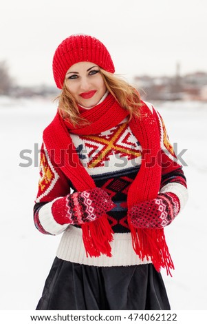Young happy beautiful blonde girl on the background of a winter landscape. The girl knitted sweater, red hat, scarf and gloves.