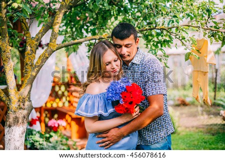 young happy beautiful couple in love walking together on grass and trees park landscape on sunset in summer with man holding his wife with pregnant belly in family concept