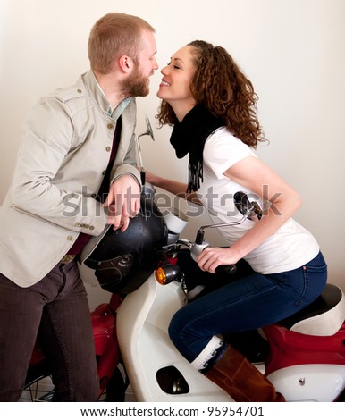 Young happy beautiful couple on the scooter flirting during date. Red and white scooter indoors. Having fun.