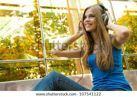 Young, happy beautiful girl with headphones - stock photo