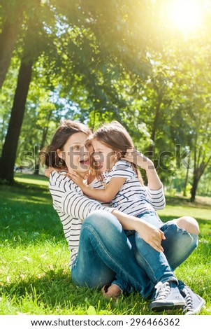 Young Happy Beautiful Mother and Daughter have Fun in Sunny Day on Meadow - stock photo