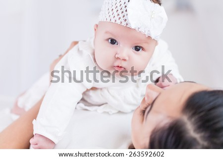 Young happy beautiful mother with her little baby - stock photo