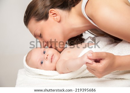 young happy beautiful mother with her little baby wrapped into the towel against white background