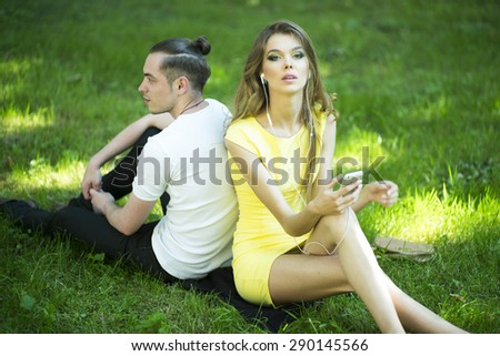 Young happy beautiful pair relaxing in park sitting on green grass listening music on natural background, horizontal picture - stock photo