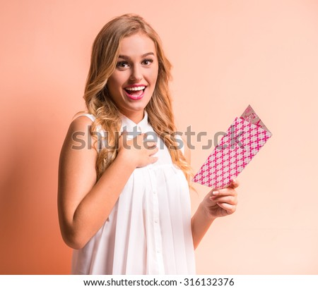 Young happy beautiful woman is reading postcard. - stock photo