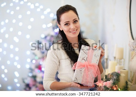 Young happy beautiful woman with gift boxes stands near Christmas tree in the room of the house.  Merry Christmas and New Year. - stock photo
