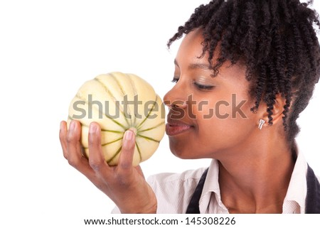 Young happy black / african american woman smelling a fresh melon isolated on white background - stock photo