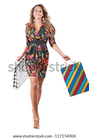 Young happy blonde woman in black dress with colorful shopping bags on a white background - stock photo