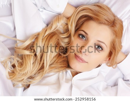 Young happy  blonde woman in the bed - stock photo