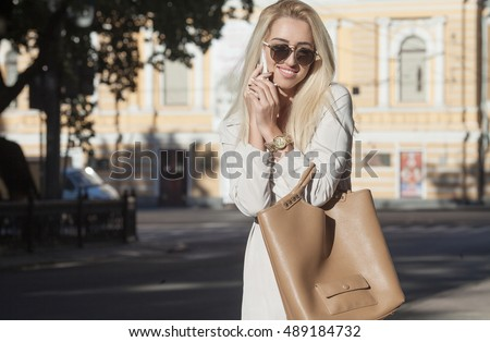 Young happy blonde woman talking on mobile phone