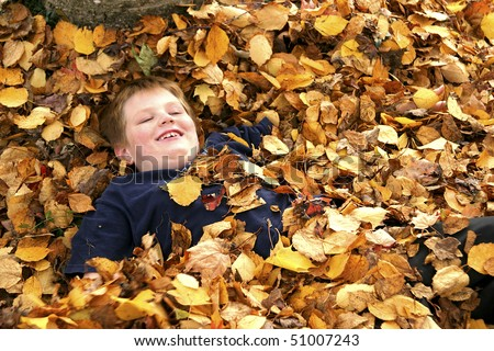 Young Happy Boy in Pile Of Autumn Leaves - stock photo