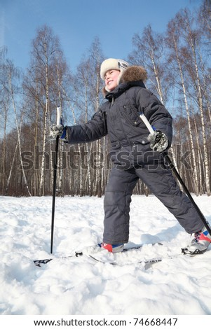 Young happy boy skates on cross-country skis with poles inside winter forest at sunny day
