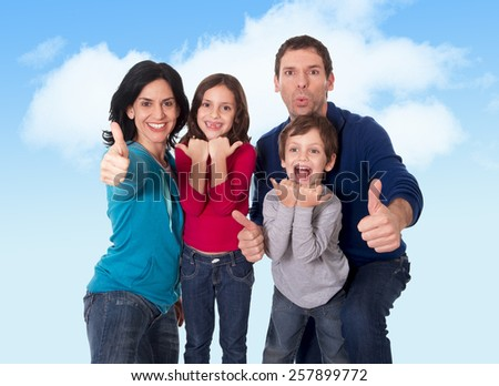 young happy Brazilian mother and father playing with little son and daughter having fun all together outdoors on a blue sky with clouds in family love and new generation concept