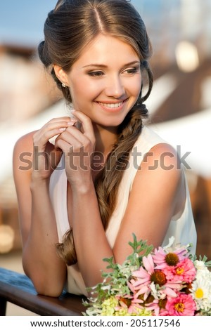 Young Happy Bride With Flower Bouquet in the summer garden - stock photo