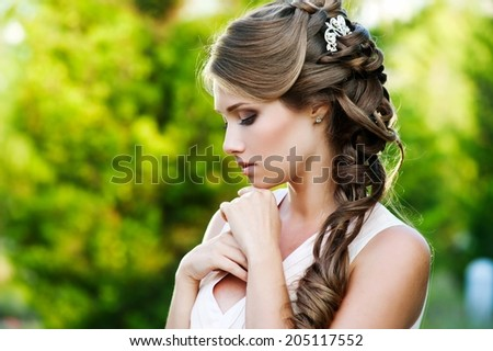 Young Happy Bride With Flower Bouquet in the summer garden
