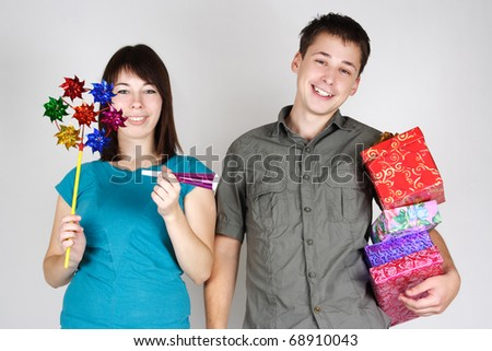 young happy brunette man and girl holding many gifts and other party items and smiling - stock photo