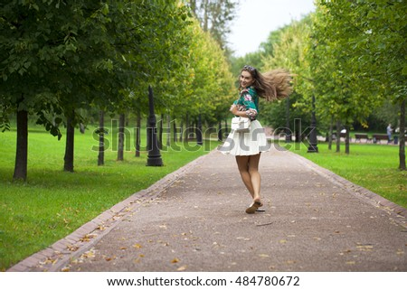 Young happy brunette woman in white skirt and blouse, summer park outdoors