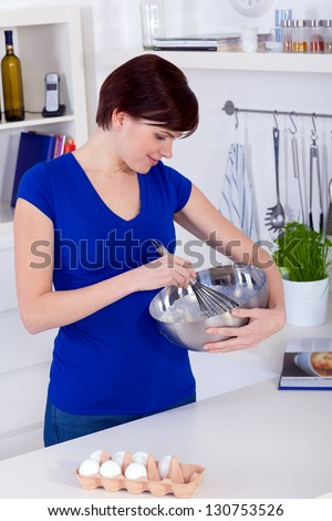 Young happy brunette woman preparing dough for a cake in a kitchen