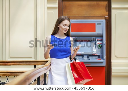 Young happy brunette woman withdrawing money from credit card at ATM, indoor shop - stock photo