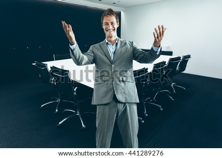 Young happy business man in suit in modern corporate conference room